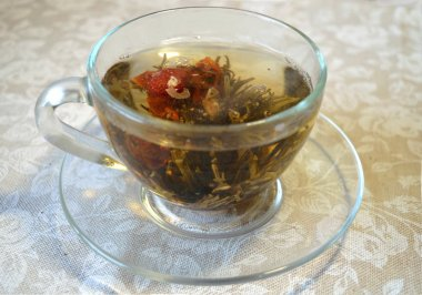 Flowering tea in the transparent cup on transparent saucer and on tablecloth with white roses