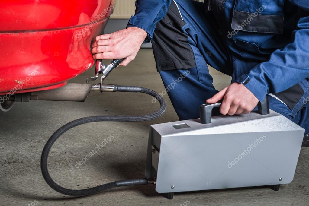 A Diagnostic Sensor Is Applied To The Ehaust Of A Car By A Mechanic