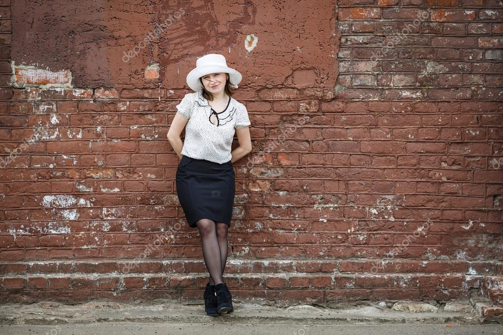 Pretty Young Brunette Woman In A White Hat Blouse And Black Skirt Posing Outdoor Old Vintage Brown Brick Wall Background Girl Is Leaning Against The