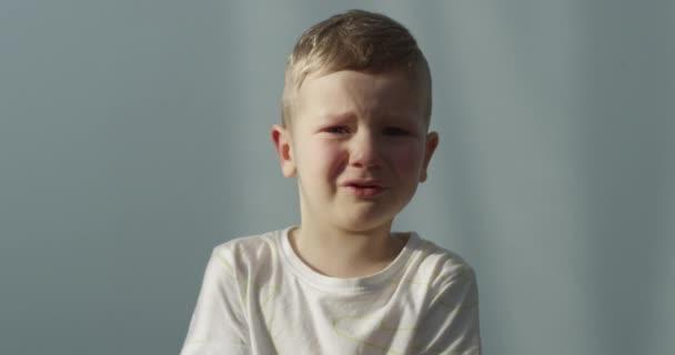 Portrét malého chlapce plačícího v interiéru pořízen na červené kameře