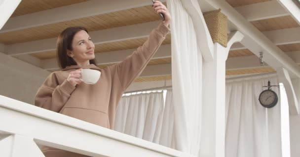 Beautiful Woman Having a Cup of Coffee and Making Selfie Standing on a Terrasse Shot on Red Camera