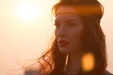 Portrait of a hippie woman with headband looking far away at sunset with windy hair.