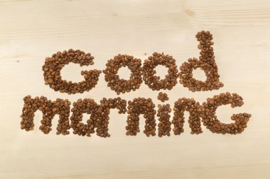 Phrase good morning made with coffee beans on a table top view