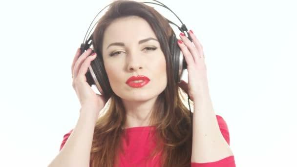 Szép nő visel piros rúzs, hallgatta a zenét, megható nagy fejhallgató leveszi a fül csésze, mondván, hogy mi elszigetelt fehér background közepes lövés