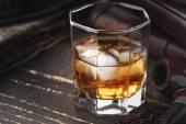 Fotografie Whisky mit Eis und Rohr auf den Holztisch