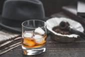 Fotografie Whisky mit Eis, Pfeife, Hut und Zeitung horizontal