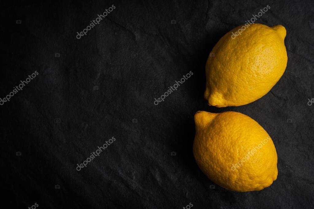 Yellow lemons on the black stone table horizontal