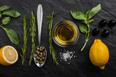 Green basil and rosemary with salt , lemons , capers , olives and olive oil on the black stone  table stock vector