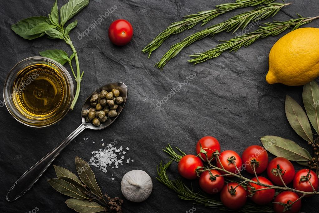 Herbs mix with tomatoes, lemon and olive oil on the black stone table