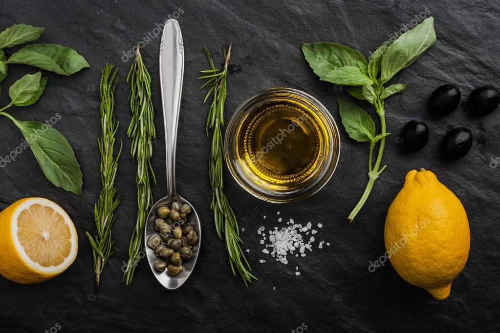 Herbs mix with  lemons , capers and olives on the black stone table