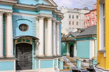 Blue church with white pillars in the middle of colorful houses