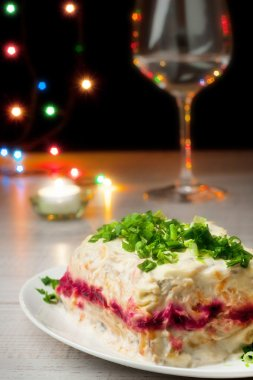 Herring salad with glass of chanpagne and lights