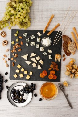 Cheese platter with different fruits and nuts top view