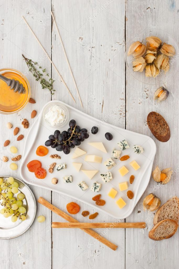 Cheese platter with different fruits , nuts and honey top view