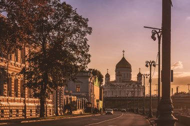 Street with old houses and church at sunset