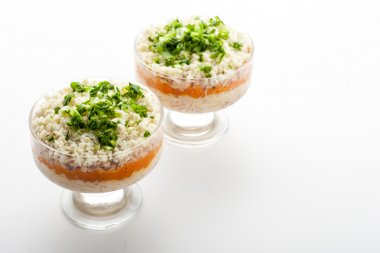 Layered salad with eggs and fish on the glass dish horizontal