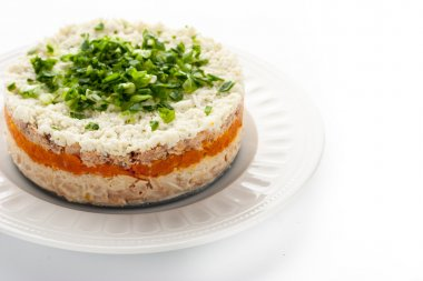 Layered salad with eggs and fish on the white background