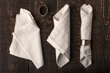 Set of the napkins with vintage rings on the wooden table top view