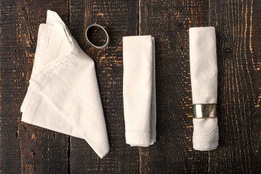 Set of the napkins with vintage rings on the wooden table