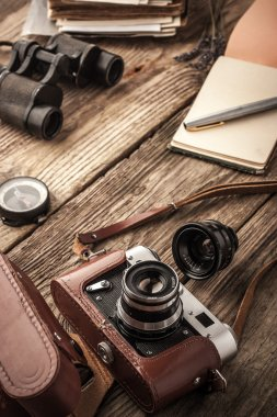 Camera with notebook and binoculars on the wooden table vertical