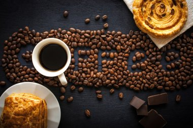 Coffee word made by coffee beans with chocolate , pastry and cup of coffee