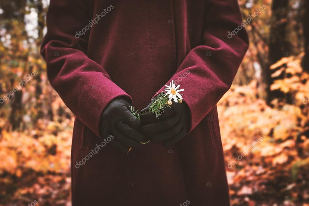 Woman with flower in the hand in the autumn forest