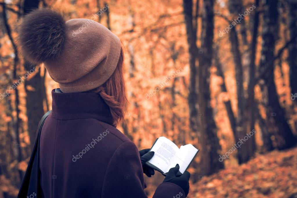Women with book in the autumn forest