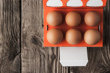 Chicken eggs in a paper box on a wooden table