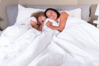 two attractive women going to sleep in bed