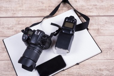 Photographers workplace with book, phone and camera on wooden ta