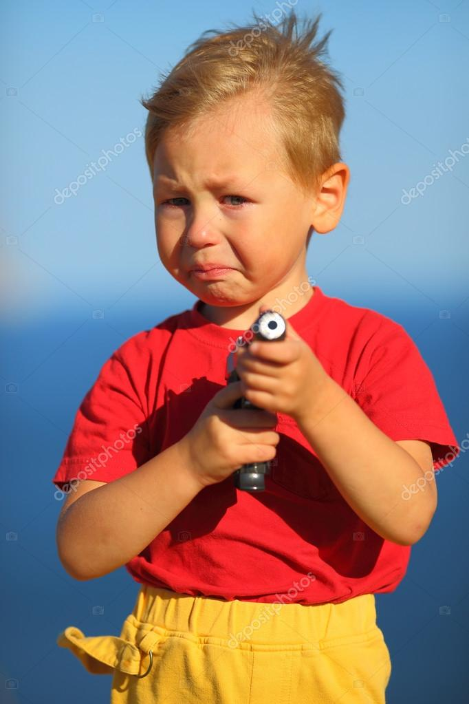 Crying Boy With A Gun On The Coast Stock Photo