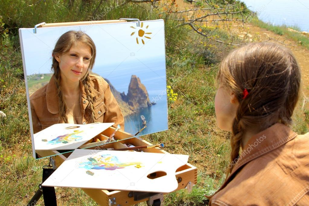 girl artist draws on a mountain coast