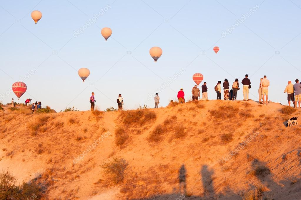 Group of tourists watching balloon fly on top of mountain