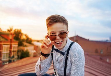 Young bold girl woman in hipster clothes, sitting on roof showin