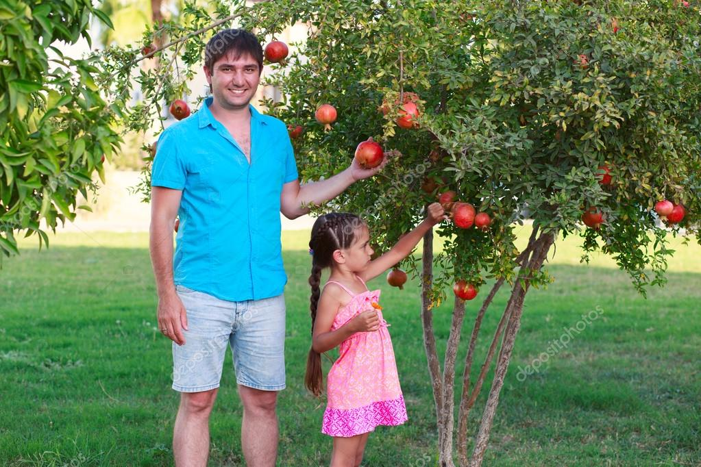 Family in garden on background of pomegranate tree