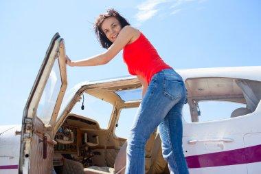 Pilot girl entering cabin of little plane
