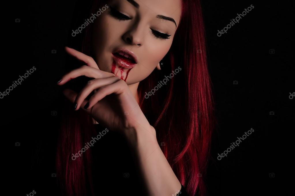 Vampire woman with blood on her face and red hair against black