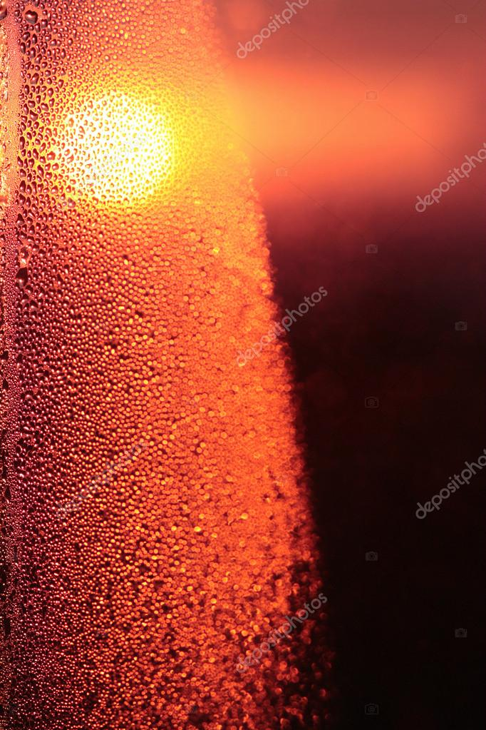 Sunset, drops of water on the sweaty glass
