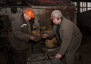 Donetsk, Ukraine - February, 20, 2013: Locksmiths repair mining equipment