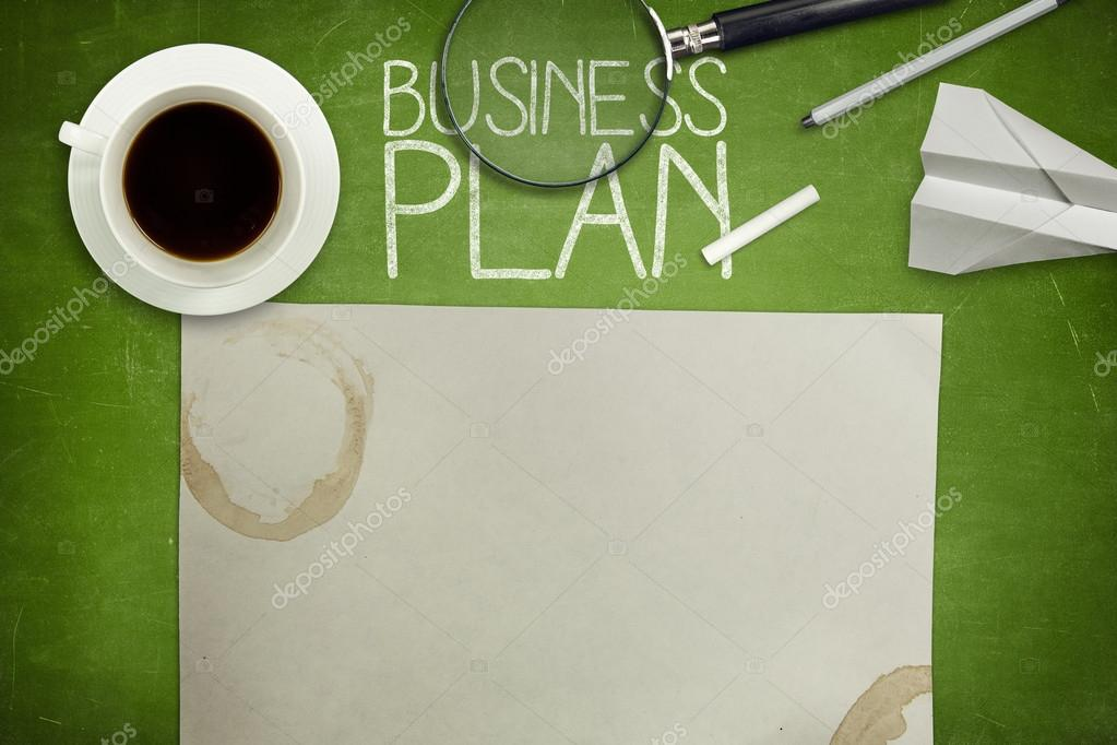 Business plan concept on green blackboard with coffee cup
