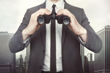 Businessman holding binoculars with tie and shirt on cityscape background stock vector