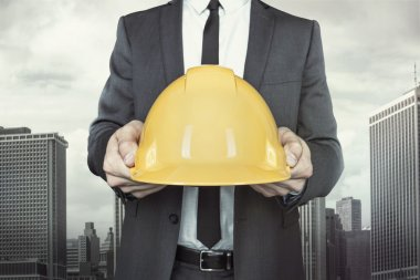 Businessman holding yellow helmet in hands on cityscape background