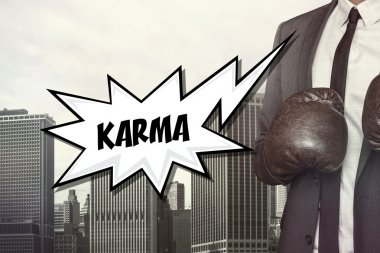 Karma text with businessman wearing boxing gloves