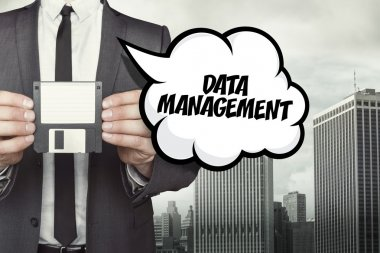 Data management text on speech bubble with businessman holding diskette