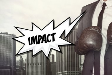 Impact text with businessman wearing boxing gloves