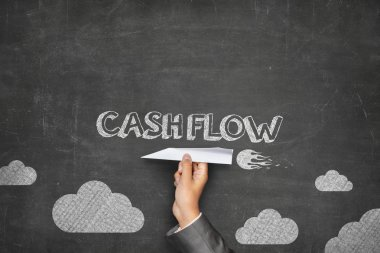 Cash flow concept on blackboard with paper plane