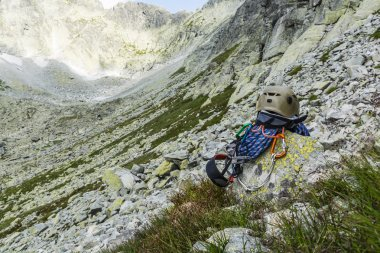 Rope, helmet, carabiners, climbing harness and descender on a rock in the valley