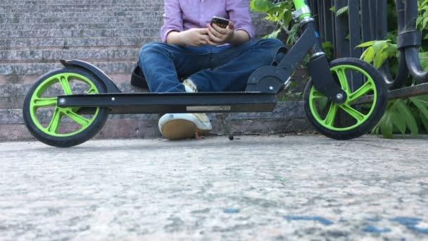 Fiú ül a parkban, és írja a telefon a lépcsőn