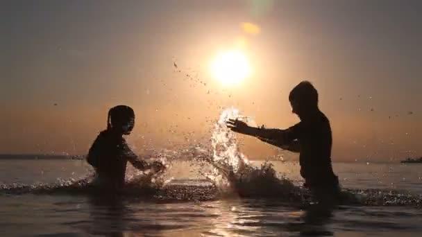 Kinder sprühen Sie Wasser bei Sonnenuntergang