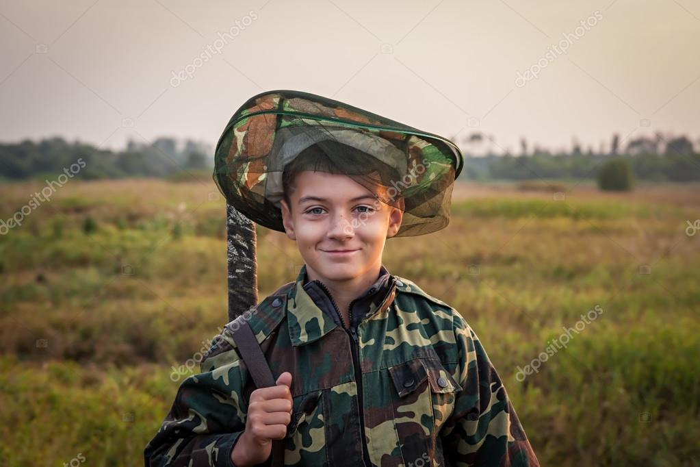 Young smiling boy with hunting shotgun standing at green field during sunset